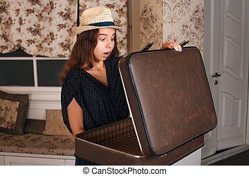 Female holding a half-open suitcase in her hands.