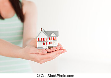 Female holding a miniature house while standing