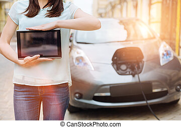 Female holding a tablet in front of her car