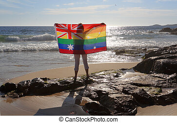 Female holding an Australian flag in rainbow colours