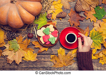 Female holding cup of coffee near cookies on autumn background.