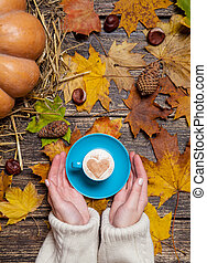 Female holding cup of coffee on autumn background.