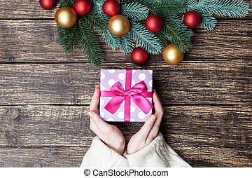 Female holding gift box on a table.