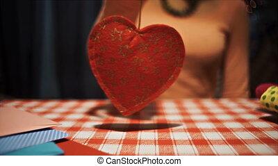 Female holding heart pendulum in hands, weak broken love symbol