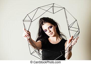 Female holding model of geometric solid