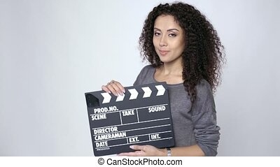 Female holding movie clapper board - Smiling curly female...