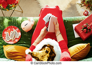 Holiday season. elegant female in sparkle gold sequin santa hat holding purse with money and credit cards and planning Christmas budget while sitting on divan in the modern living room at Christmas.