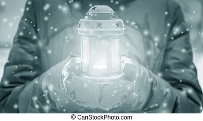 Female holding candle lantern with luminous light in winter during snow fall close up. Winter Fairy New Year Christmas. Cinemagraph seamless loop animation motion render background. White blue color
