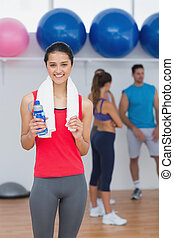 Female holding water bottle with fitness class in background