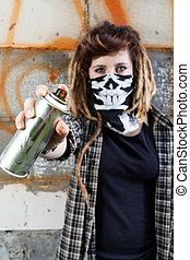 Female hooligan holding graffiti spray