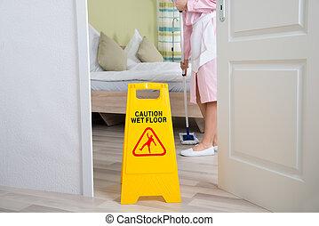 Female Housekeeper Cleaning Floor