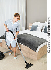 Female Housekeeper With Vacuum Cleaner