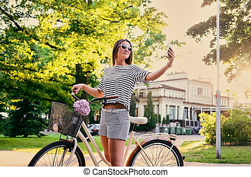 Female in a park on a bicycle making selfie.