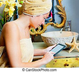 Female in bathroom reading ebook tablet