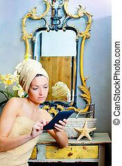 Female in bathroomreading ebook tablet