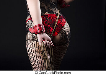 Female in BDSM Sexy Lingerie Posing with Rope Accessory for BDSM Role Play. In red Handcuffs and Net Pantyhose.