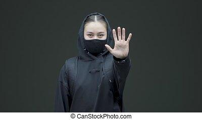Female in black mask show defensive hand gesture. Gender discrimination protest against abuse, domestic violence. High quality 4k footage
