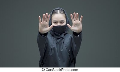 Female in black mask show defensive hands gesture and goes. Gender discrimination protest, fight for womens rights. High quality 4k footage