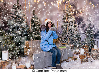 Female in blue down jacket blows snowflakes while sitting on a swing with a blanket under the flashlights in a snow-covered park