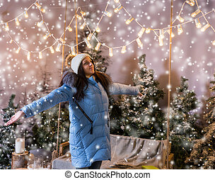 Female in blue down jacket rejoicing because of snowing standing near a swing with a blanket under the flashlights in a snow-covered park