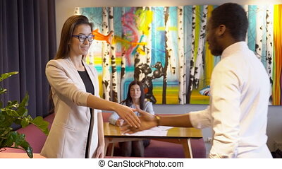 Female in glasses welcome African man and shakes hand with...