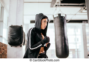 female in hoodie is looking at opponent and doing karate kicks