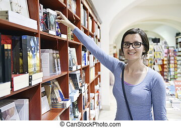 female in library - Pretty female student standing at...