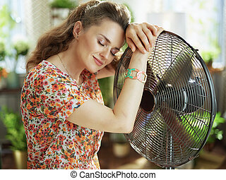 female in modern house in sunny hot summer day fanning herself
