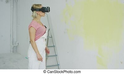 Female in overalls using virtual reality headset - Side view...