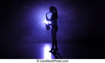Female in smoky studio plays on saxophone, silhouette. Slow motion