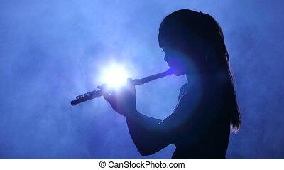 Female in spotlight in smoky studio plays on flute, silhouette