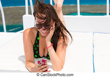 Female in swimsuit lying on the deck of the yacht and takes...