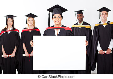female Indian graduate holding white board with classmates...