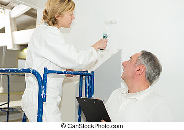 female industrial painting apprentice painting the wall white