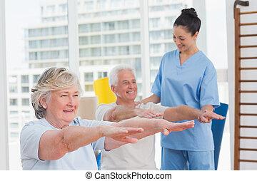 Female instructor assisting senior couple to exercise