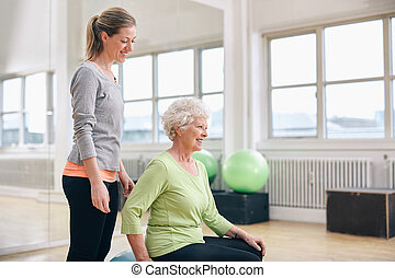 Female instructor assisting senior woman exercising in gym