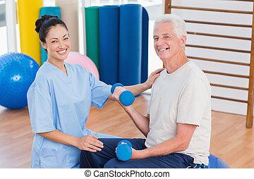 Female instructor with senior man lifting dumbbells -...