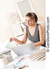 Female interior designer working holding color swatches
