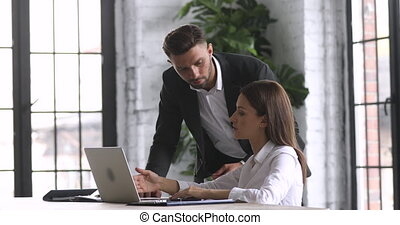 Female intern learning computer software talking to mentor ...