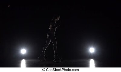 Female is dancing in kangoo jumps shoes on black background