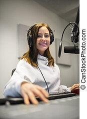Female Jockey Smiling While Wearing Headphones In Radio Studio