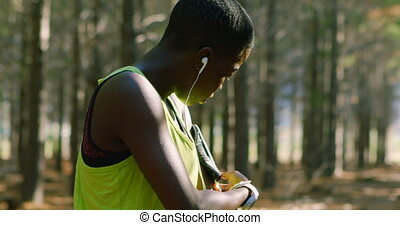 Female jogger adjusting arm band in the forest 4k - Female...