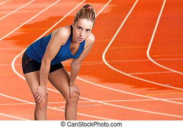 Female jogger resting after a long run on a wet athletics running track