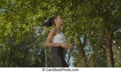Female jogger running during outdoor workout in park