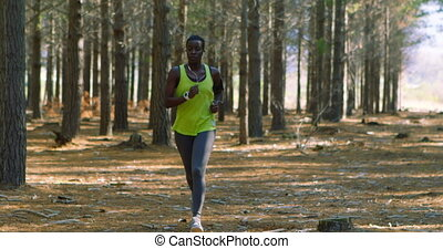 Female jogger running in the forest 4k