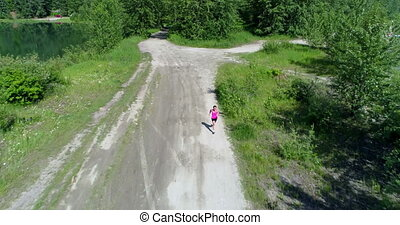 Female jogger running on the forest path 4k - Aerial of...