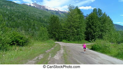Female jogger running on the forest path 4k - Female jogger...