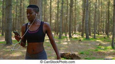 Female jogger using mobile phone while jogging 4k - Female...
