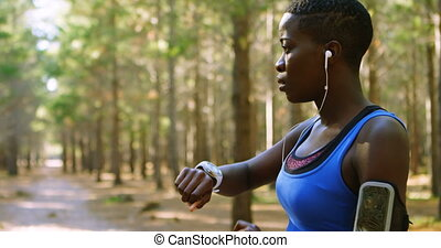 Female jogger using smartwatch in the forest 4k - Female...