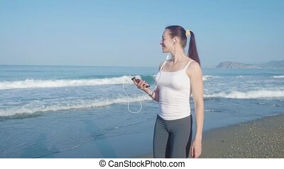 Female jogger walking and listen to the music on the beach